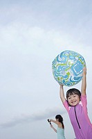 Young girl outdoors at beach holding ball with woman in background taking picture