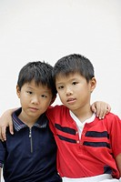Twin boys indoors with arms around shoulders