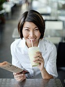 Businesswoman in cafeteria with newspaper