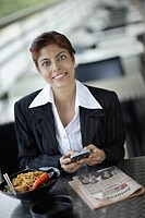 Businesswoman on outdoor patio with personal digital assistant and lunch
