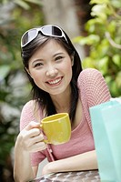 Woman on outdoor patio with shopping bag and mug
