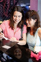 Two women in restaurant paying check