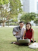 Two businesspeople outdoors in park with laptop