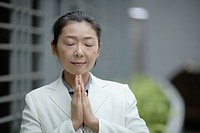Businesswoman indoors with hands together in prayer