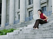 Businesswoman outdoors on staircase with laptop