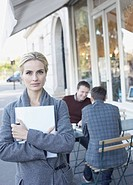 Woman outdoors holding laptop with two men nearby on patio