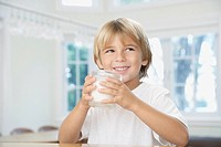 Young boy in kitchen drinking glass of milk