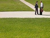 Two businesspeople outdoors on sidewalk talking