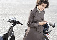 Woman outdoors leaning on her scooter and holding her mobile phone