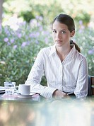 Businesswoman at outdoor patio table looking at camera
