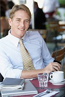 Businessman at outdoor patio table looking at camera