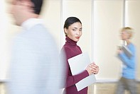 Businesswoman in office holding folder with co-workers going by