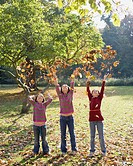 Three young girls outdoors throwing leaves in the air