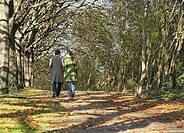 Couple outdoors walking on a path in a park