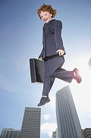 Young boy outdoors in business suit jumping in air