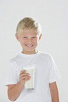 Young boy indoors holding a glass of milk