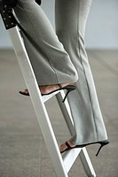 Businesswoman´s legs going up ladder
