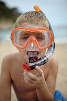 Young boy on beach wearing snorkel mask