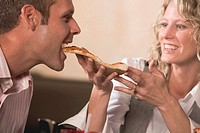 Woman feeding man pizza in restaurant