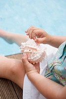 Child holding sea shell on edge of swimming pool
