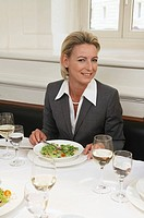Woman in elegant suit eating in a restaurant