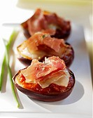 Baked stuffed aubergines topped with raw ham