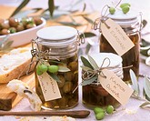 Various types of pickled olives in preserving jars