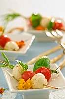 Tomatoes and mozzarella on rosemary skewers with basil