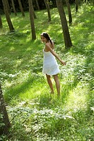 Young woman running in forest, rear view