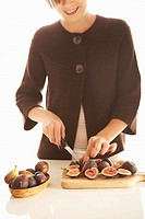 Woman slicing figs on cutting board, smiling cropped