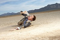 Businessman struggling on dry lake bed, drinking bottle of water