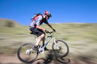 Man riding mountain bike in field, side view blurred motion