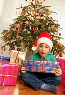 boy with Christmas presents under Christmas tree