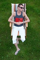 young man relaxing in a lawn chair in meadow