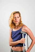Young blond woman standing and using a metal crutch