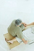 Couple sitting together on lounge chair, high angle view, cropped
