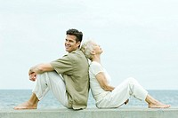 Senior woman and adult son sitting back to back by the sea, side view