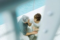 Couple sitting next to pool, high angle view, selective focus