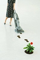 Woman vacuuming up footprints of soil, low section