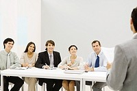 Group of professionals sitting at table, smiling, looking at man standing in foreground