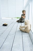 Little boy sitting on porch with arms folded, leaning against railing, looking away