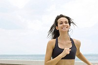 Young woman in sports bra running outdoors, smiling, looking away