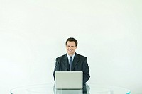 Businessman sitting, using laptop computer, smiling at camera