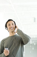 Man listening to mp3 player, hand raised, smiling at camera