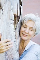 Senior woman embracing tree trunk, smiling, eyes closed