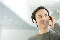 Man listening to headphones, smiling, looking away