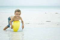 Little boy lying on top of beach ball at the beach, smiling at camera