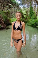 Portrait of a woman in bikini standing in a lagoon. Fraser Island, Australia