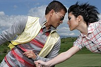 View of a couple fighting for golf club
