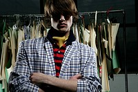 Young man standing in front of a clothing rack